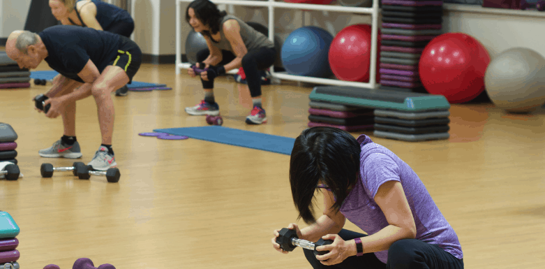 Indoor group exercise class with 3 participants and a variety of equipment