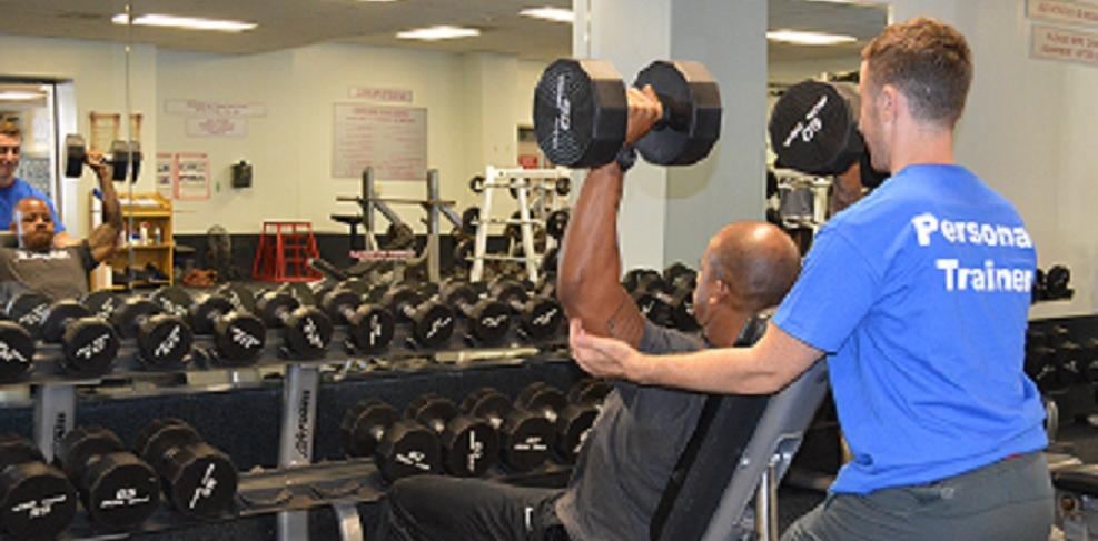 Personal Trainer spottiong a client as the client lifts free weights