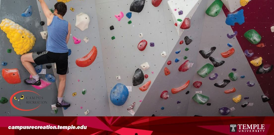 male student climbing the indoor climbing wall