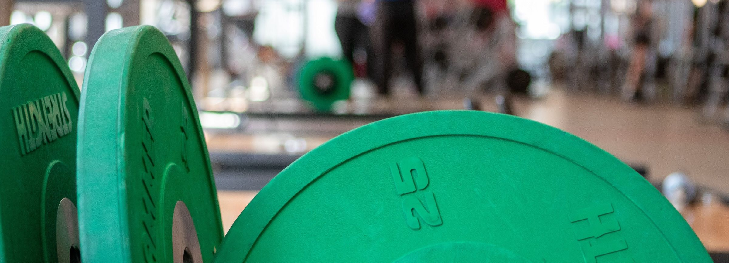 A shot of green weight plates sitting against each other in the Weight Room.