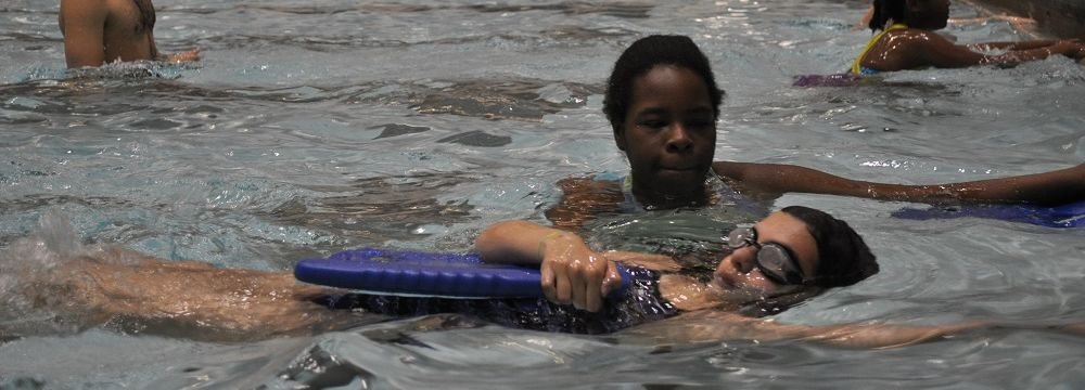 Temple student teaching a kids swim lesson