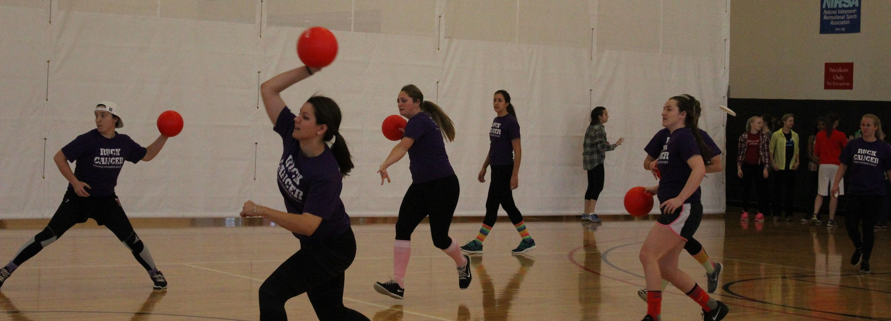A team in purple throws red dodgeballs.