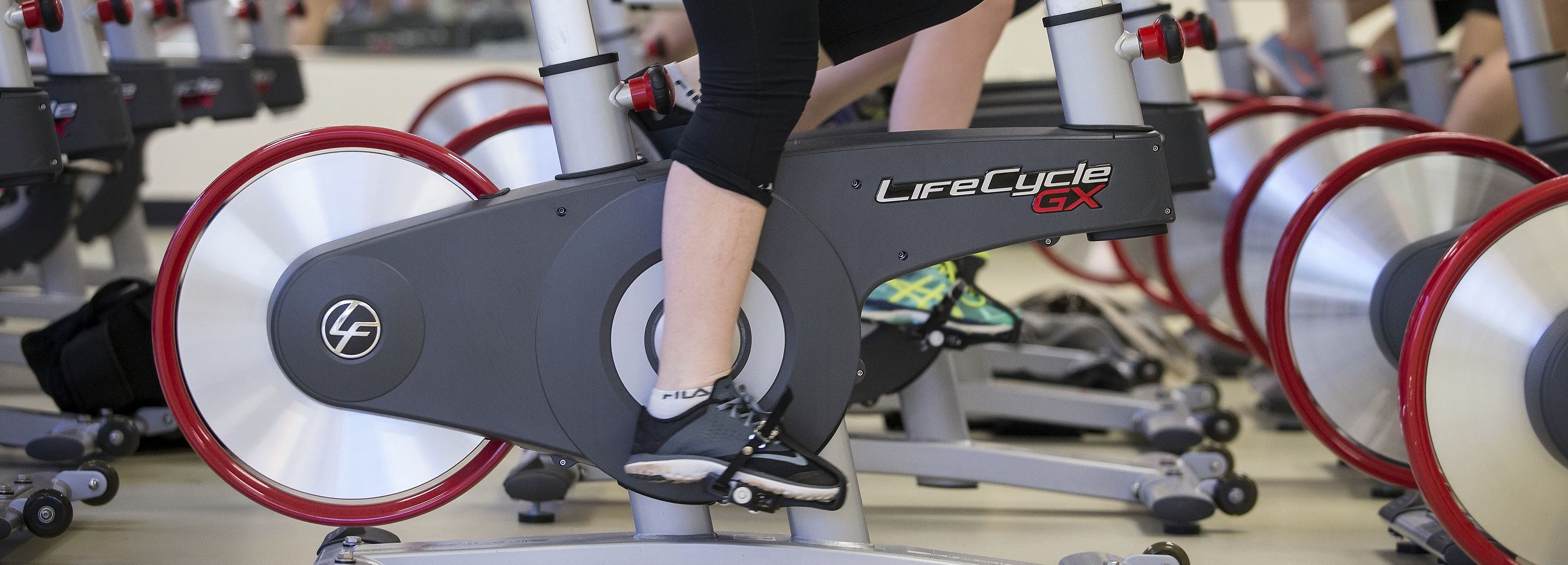 Legs pedaling during an indoor cycling session.