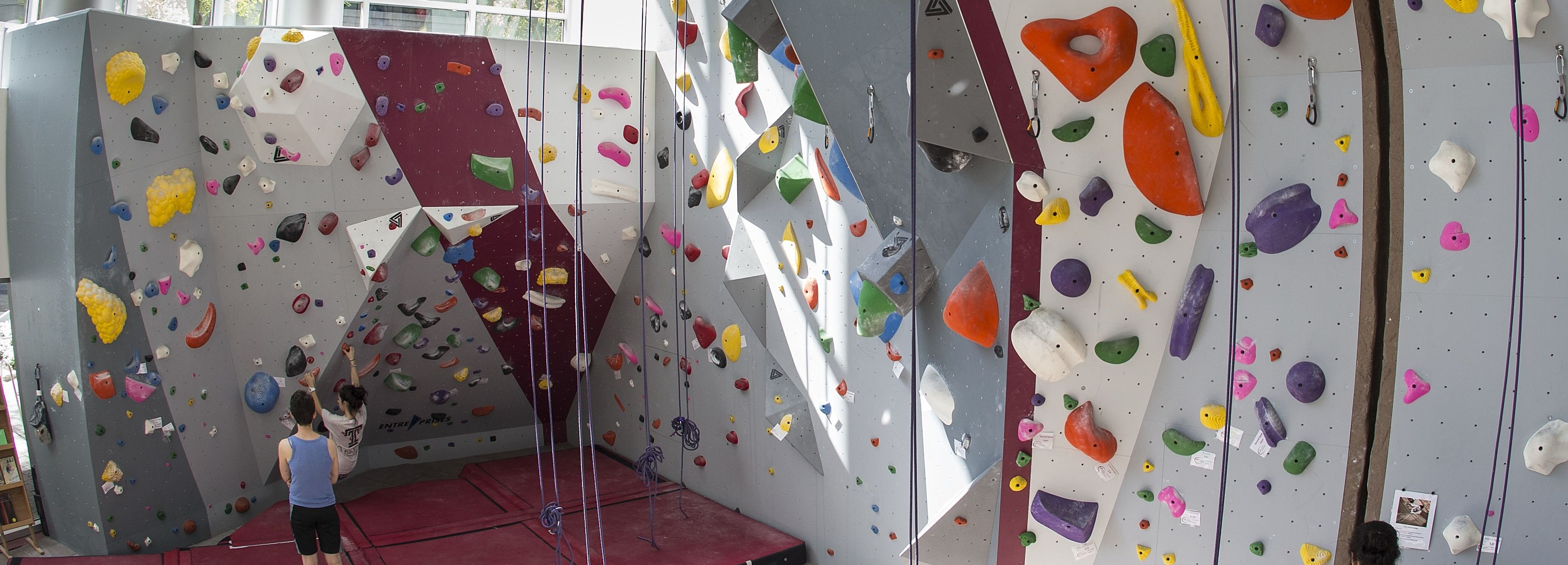 A person climbing on the wall with a spotter.