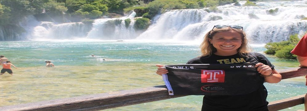 Female student holding flag in front of water fall