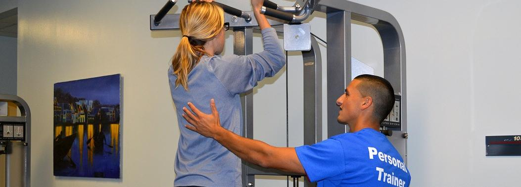 Personal Trainer helping student on an exercise machine