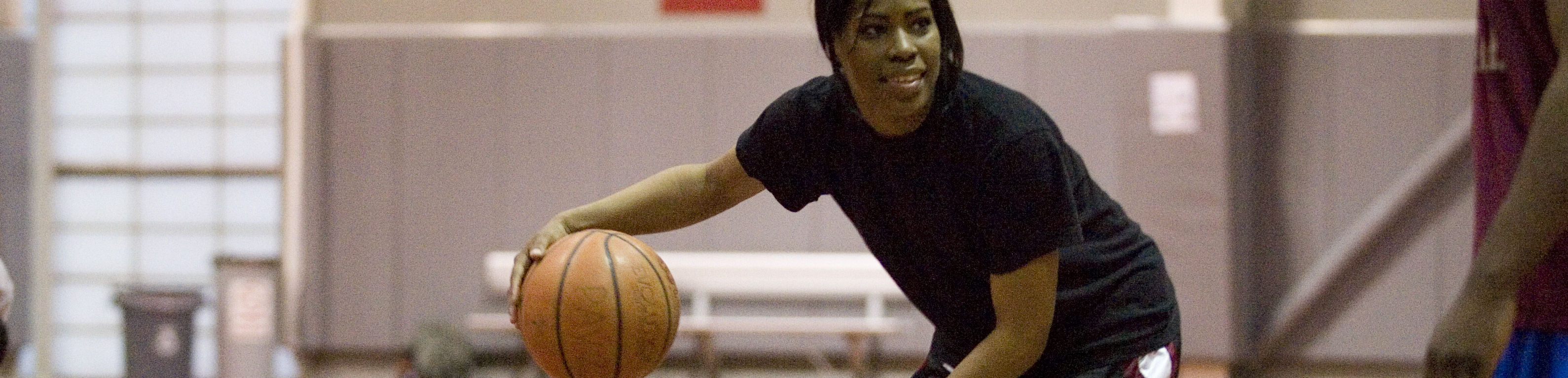 Female student playing basketball