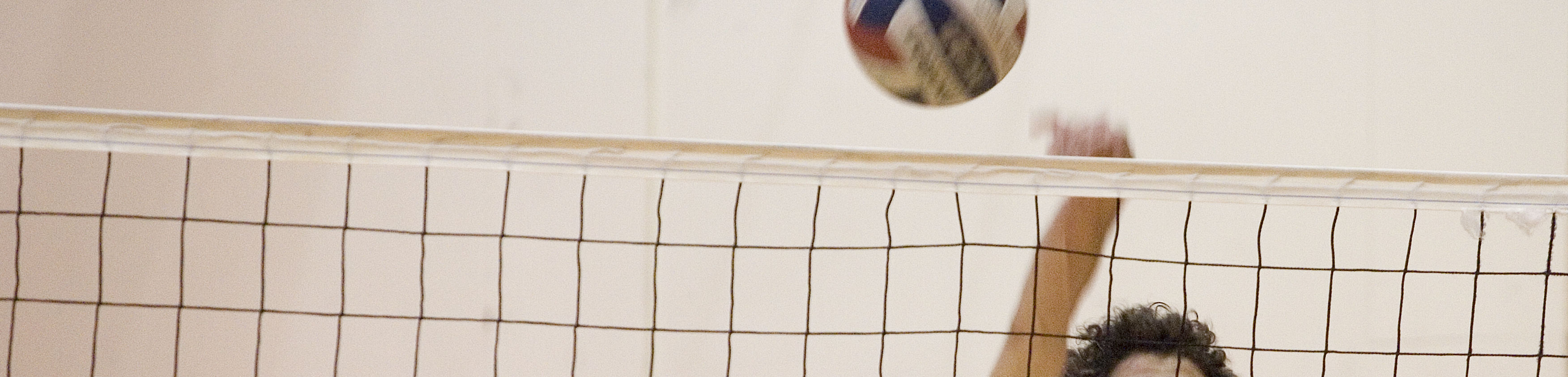 A volleyball participant hitting a volleyball over the net.