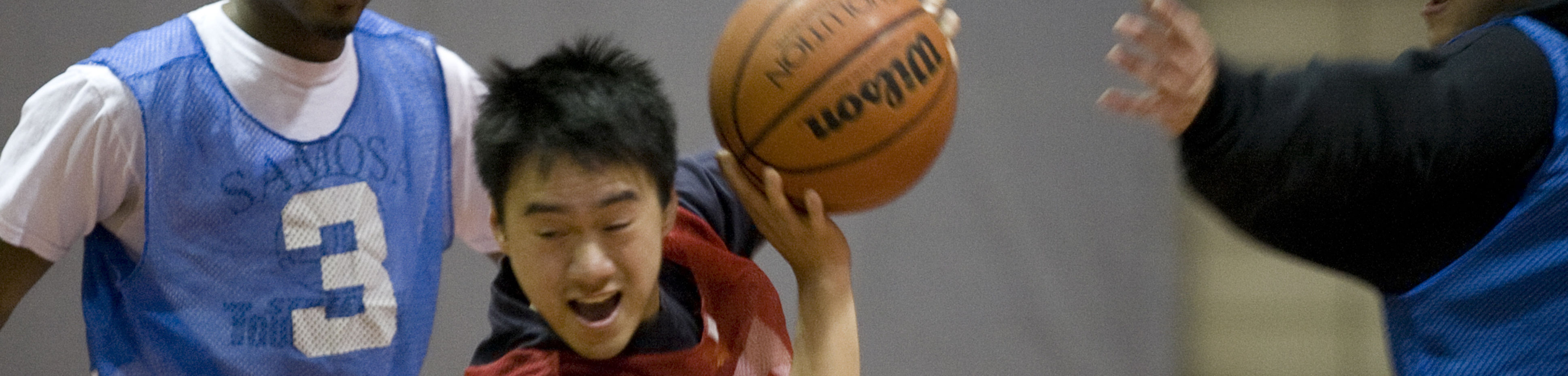 Student making a drive to the basket in a basketball game