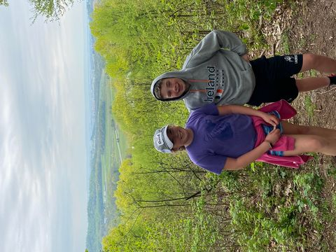 A boy and a girl stand on a hiking trail smiling, surrounded by green trees