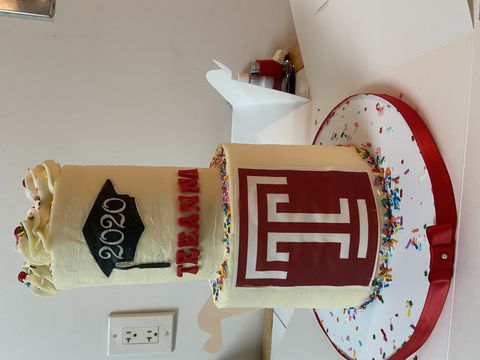 A two-layer white cake sitting on a table. The bottom layer has a large, red Temple T design. The top layer has a black graduation cap design and the name Treanna underneath the cap in red lettering.
