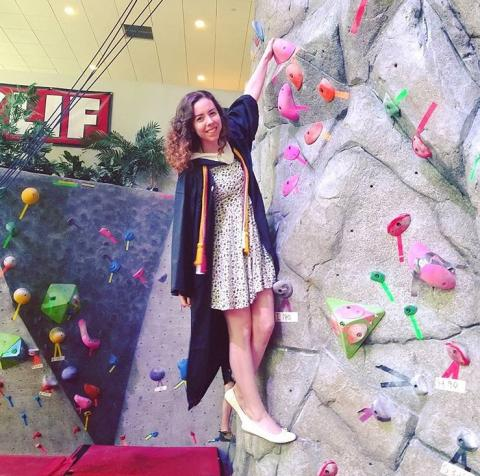 Girl hanging on climbing wall in graduation robe