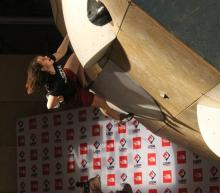 Student hanging off an indoor climbing wall