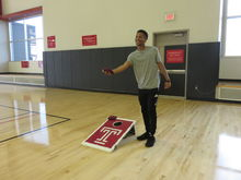 A competitor stands next to a corn hole board preparing to throw a bean bag.