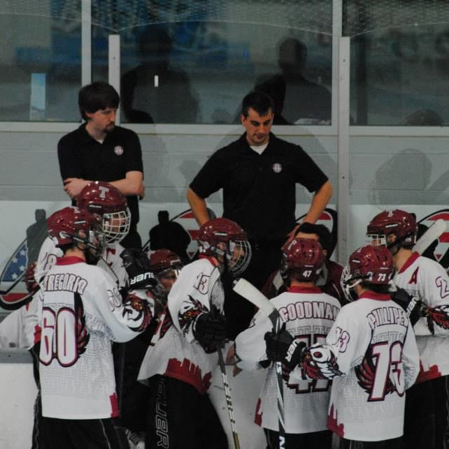Temple University Roller Hockey Club huddled up on on the ice in front of their bench.