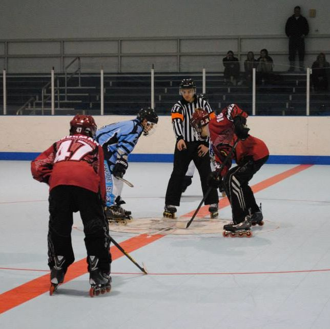 Two Temple University Roller Hockey Club members lined up at the center of the rink about to start the game.