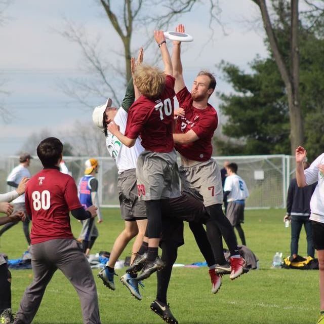 Two Temple Mens Ultimate Club members jumping into the air to catch a frisbee against an apposing player.