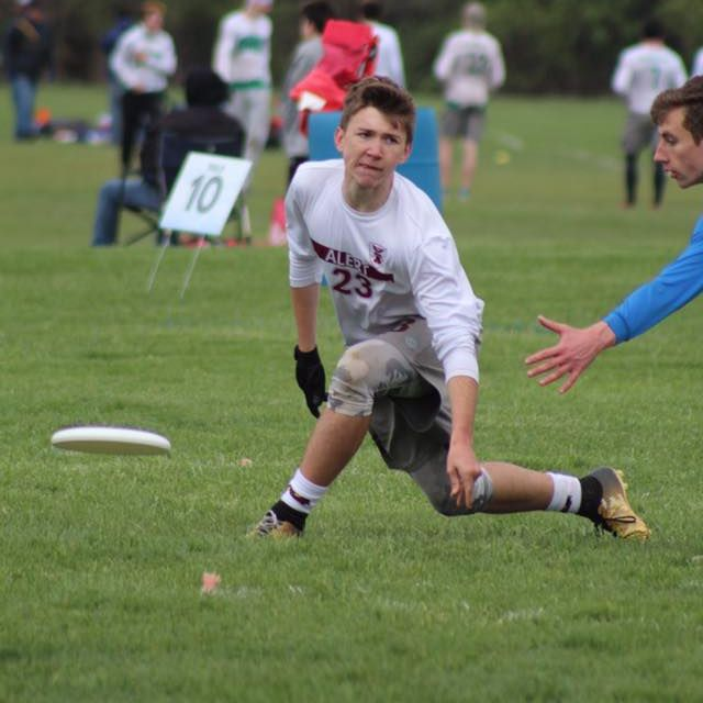 Mens Ultimate club member throwing a frisbee from a low angle around a defender.