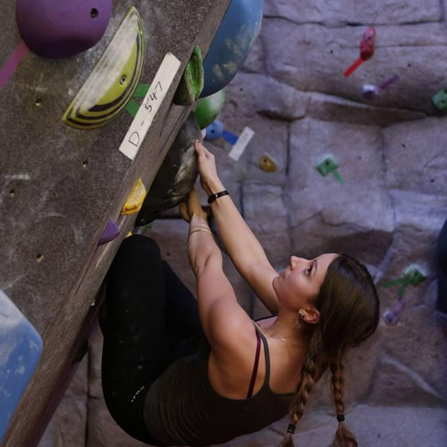 Club member scaling the bouldering wall