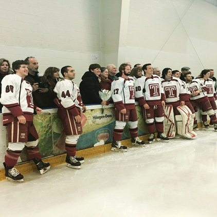 Temple University Ice Hockey Club group picture standing in front of their bench on the ice.