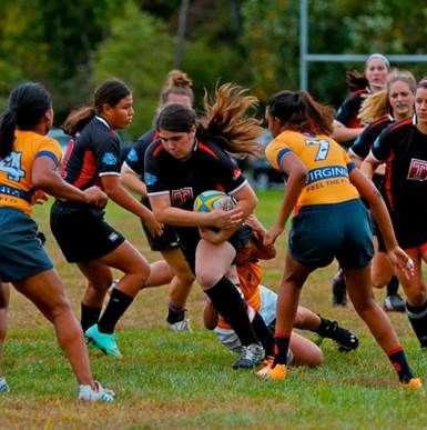 Temple University Women's Rugby Club member running with the ball through the opposing team during a game.