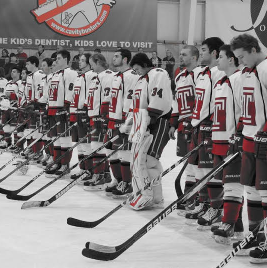 Temple University Ice Hockey Club team picture on the ice holding out their sticks. The picture is in black and white with hints of red showing.