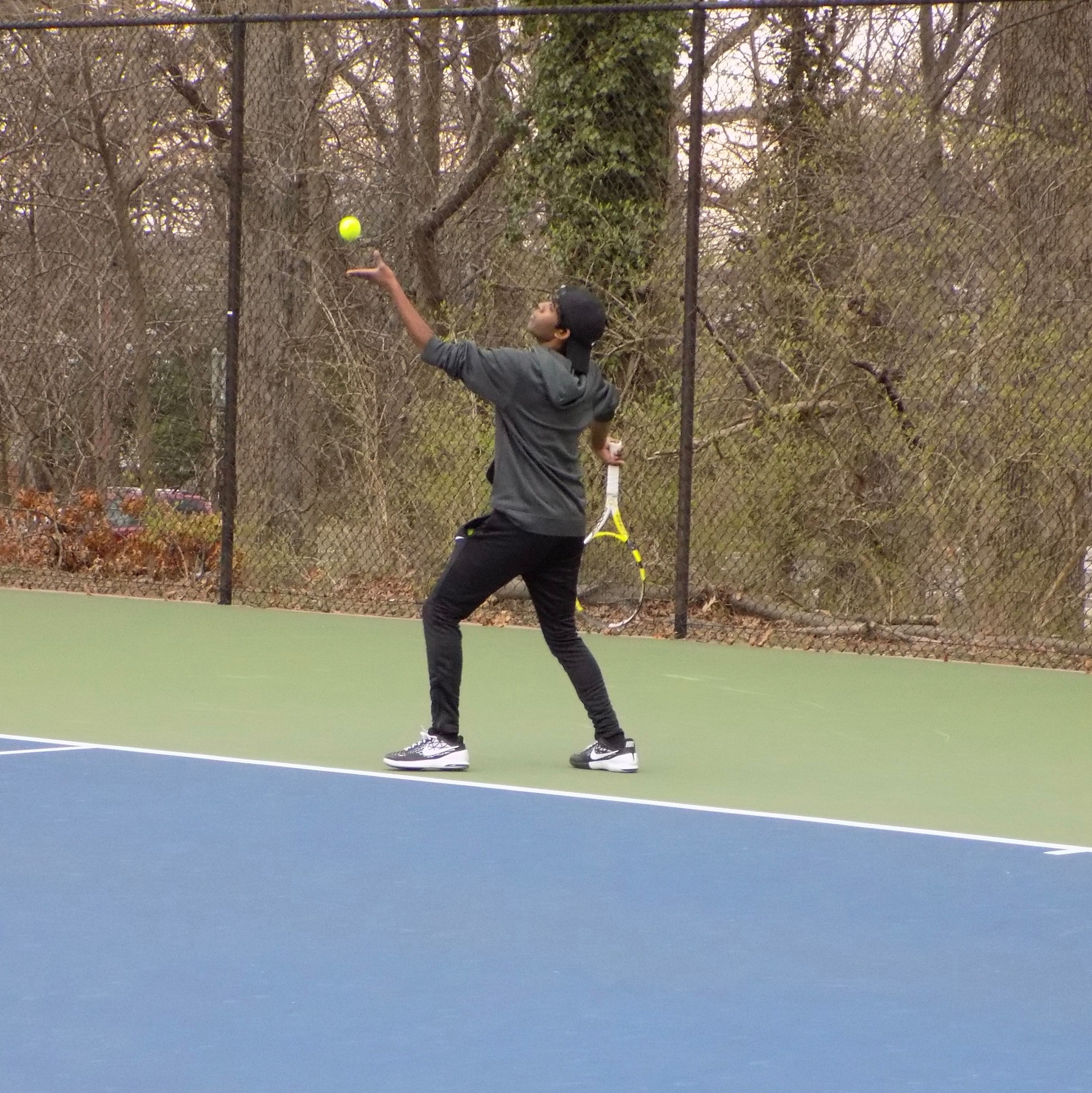 A Temple University Tennis Club member about to serve.