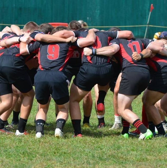 Temple University Men's Rugby Team huddled together on the field.