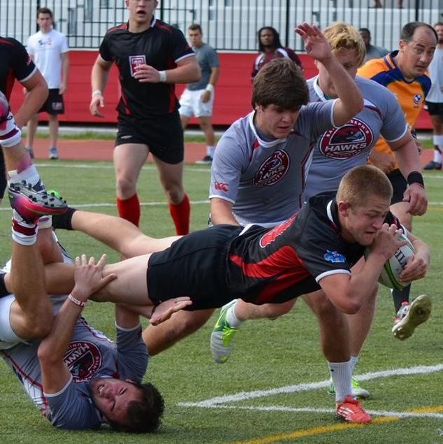 Temple University Men's Rugby Club member diving with the ball while being tackled by the opposing team.