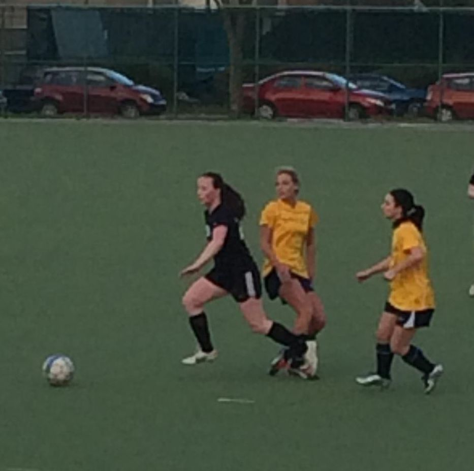 Temple University Women's Soccer Club member pulling away from two opposing club members during a game.